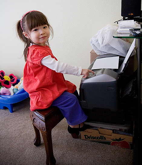 Kadie pretending to e-mail daddy with the printer - Photo by Jenni